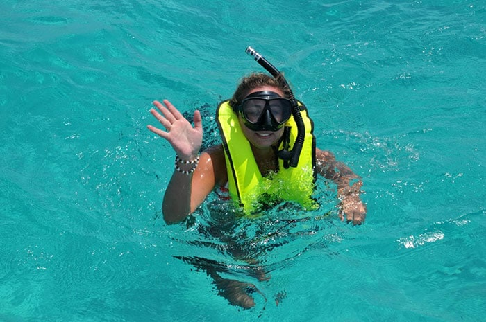 woman waving as she snorkels in the ocean of half moon cay