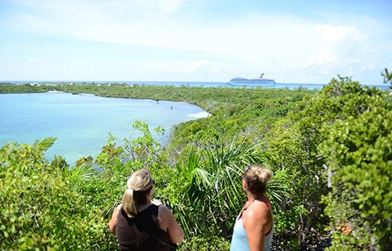 two women hiking in half moon cay admire the aerial view of the island with a carnival cruise ship in the background