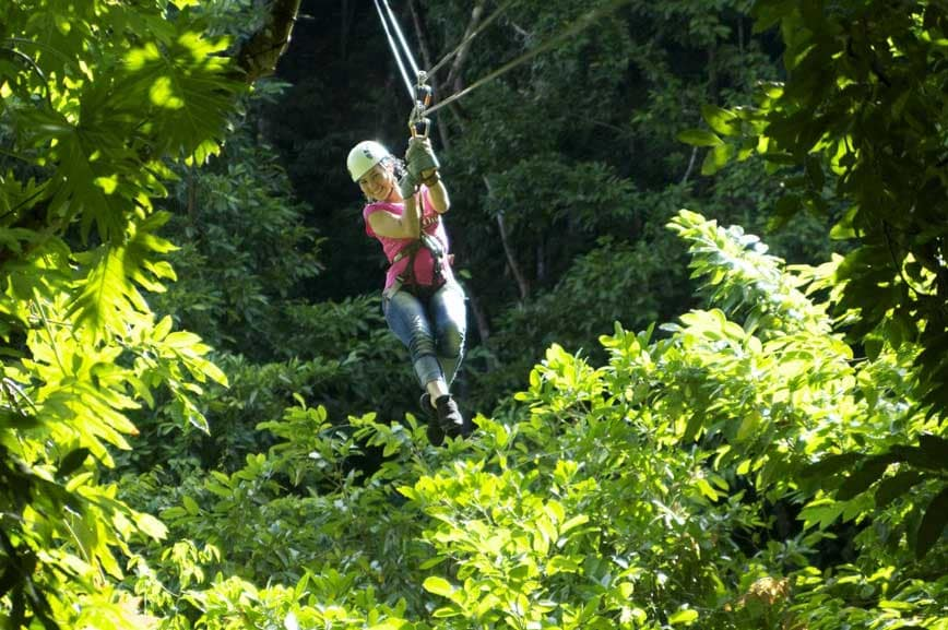 woman smiles as she zip lines over white river valley