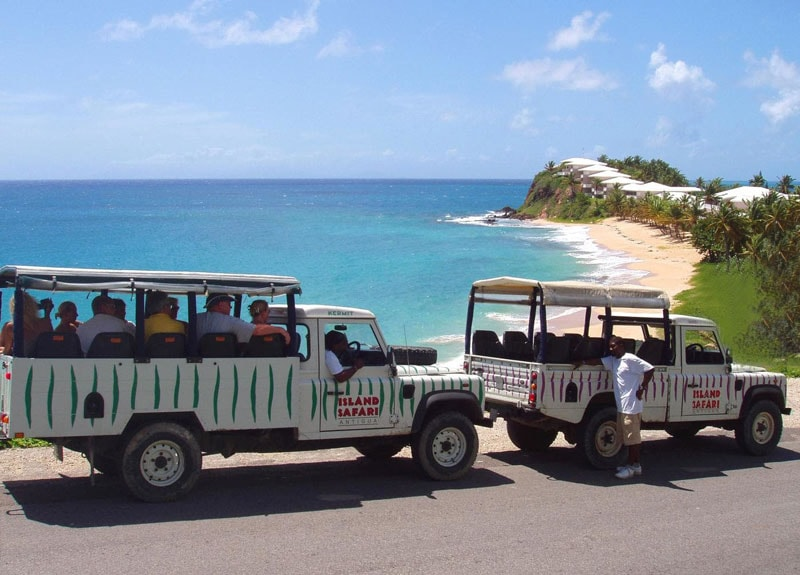 two 4x4 island safari trucks parked on a hill with antigua's coastline beach in the background