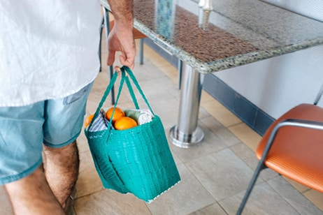 Drea's husband carries turquoise bag with oranges