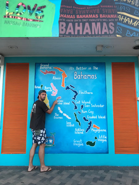 husband standing in front of Bahamas map