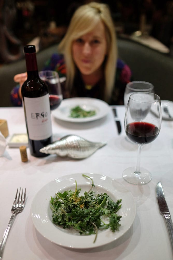 wife smiling at dinner behind wine bottle