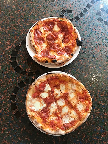 two plates of pizza on counter