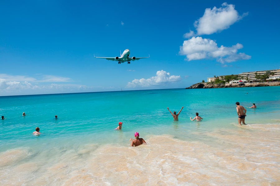 beach goers in Maho Beach stand by and watch a commercial airplane fly over them as the plane  prepares to land