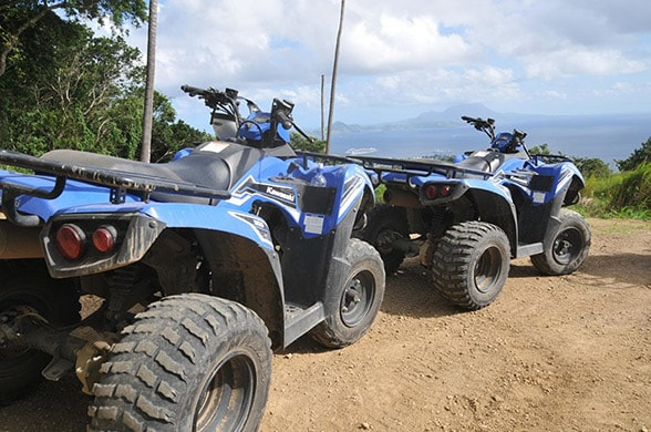 two atv's parked on the side of a dirt road in st kitts