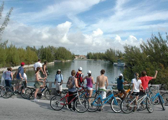 group of people stop riding their bicycles in front of a river as tour guide speaks in freeport