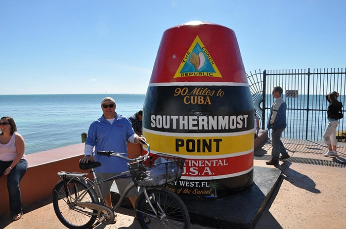 man holds his bike as he stands in front of the southernmost point of the continental usa
