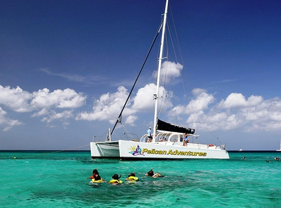 people snorkeling among the coral reefs in aruba while others are onboard a catamaran