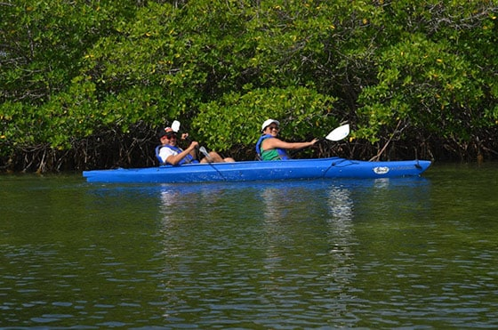 couple on a blue kayak smile as they paddle in key west