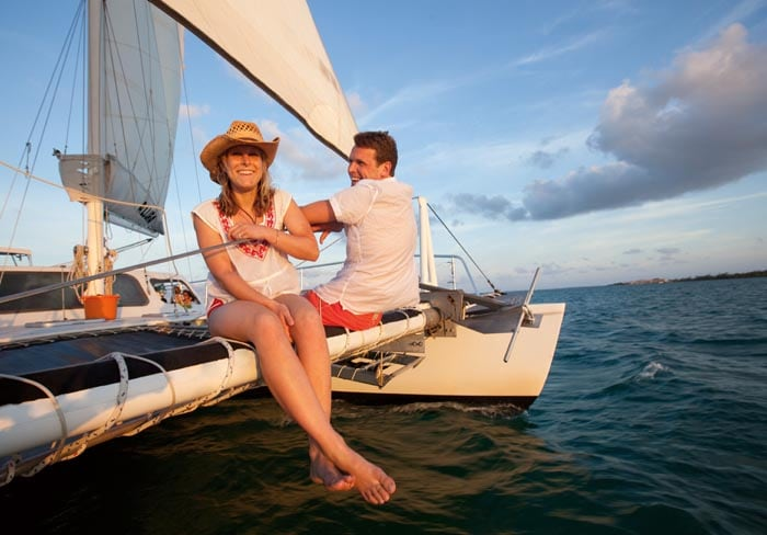 couple laughing as they sit on the edge of a catamaran off the coast of antigua