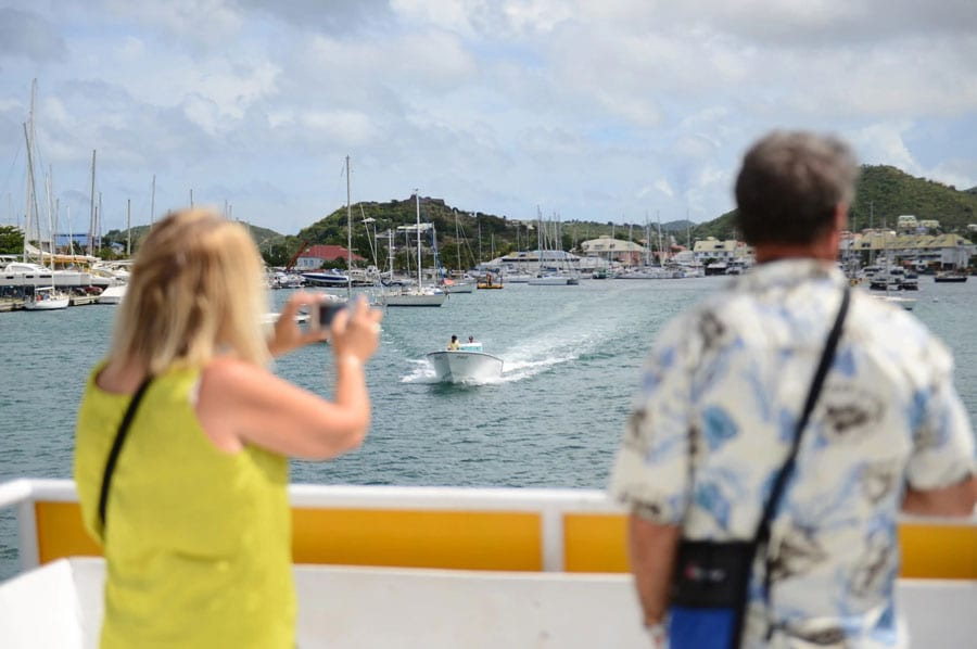 couple takes a photo of st maarten coastline during a boat tour as another boat passes by