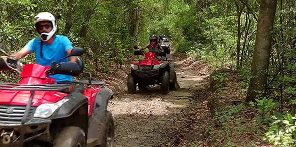 people riding red atv through dirt roads in san juan