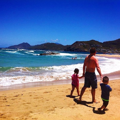 man walking along a beach in st kitts with his son and daughter