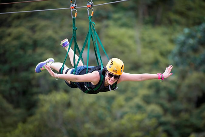 woman zip lining on the longest zip line in the world in toro verde adventure park