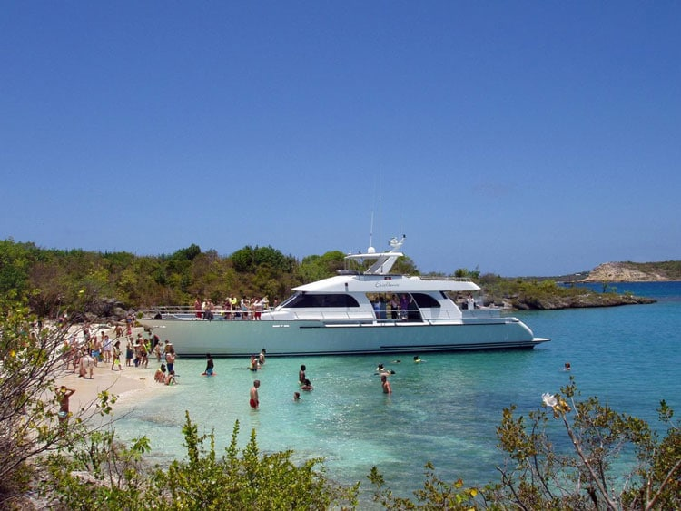 guests swimming and having fun on the beach as five star luxury catamaran is docked on green island