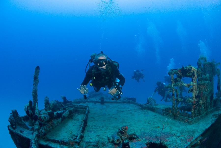 man waves as he scuba dives over a ship wreck in st maarten
