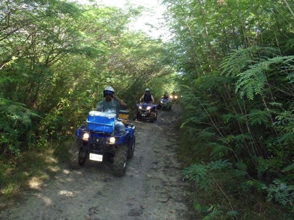 group rides atv through rugged terrain in antigua's back country