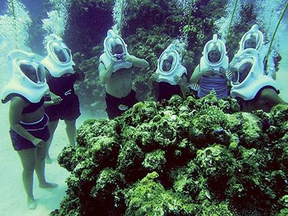 people wearing sea trek helmets, looking at coral reef in grand cayman