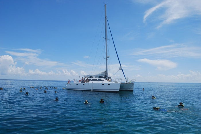 group of people snorkeling around a catamaran off the coast of freeport