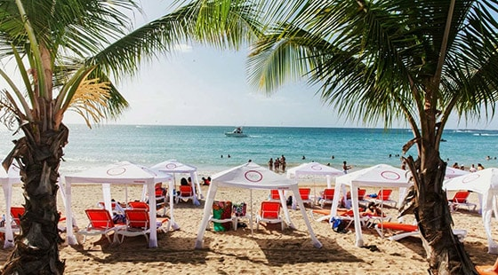 beach tents and beach chairs scattered across vivo beach club in san juan as people have fun in the ocean