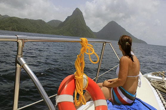 woman looking at st lucia's two pitons during a catamaran cruise