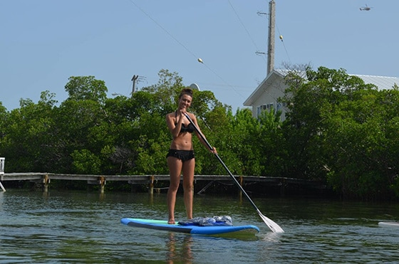 woman smiles as she paddles on a stand-up paddleboard in key west