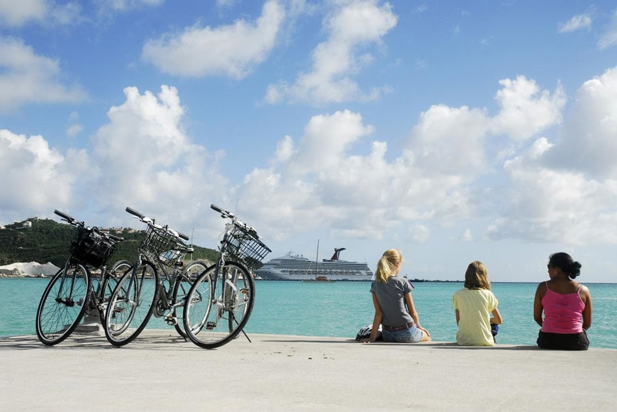 three woman take a break from bike riding and admire st maarten coast with a carnival cruise ship docks in the background