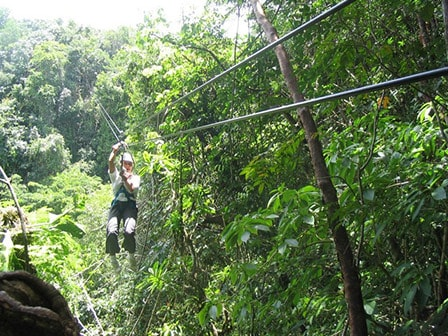 man zip lining through the veragua rainforest