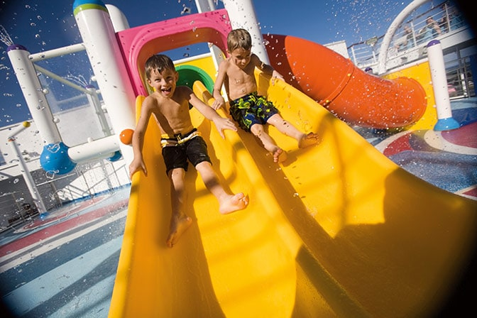 2 boys going down a yellow water slide in waterworks