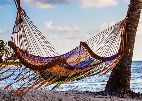 colorful hammock hanging from 2 palm trees on the beach
