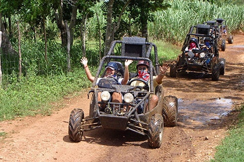 pairs of people riding dune buggies through muddy roads in the dominican republic