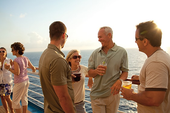 friends having a drink on a cruise deck during the sunset