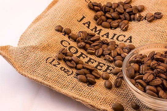 coffee beans over a 12oz bag of jamaican coffee