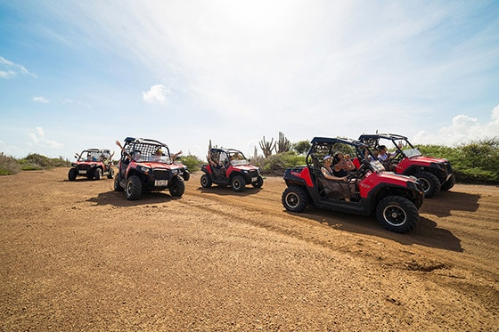group of people riding mini Jeeps along Curacao's northeast coast