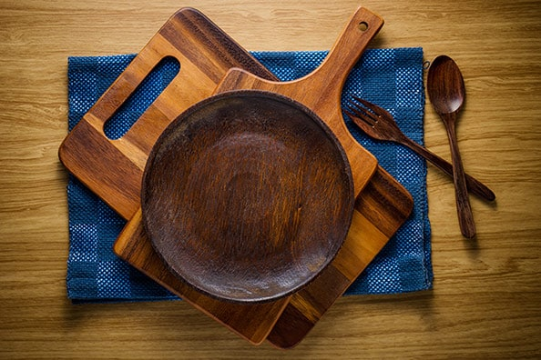 pile of wooded kitchen utensils over a blue cloth