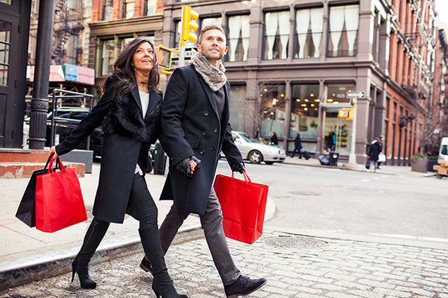 couple crossing the street with shopping bags in new york city
