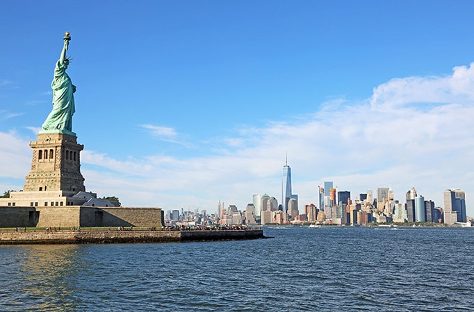 statue of liberty with new york city in the background