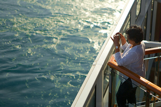 woman taking photos on the deck of a carnival cruise