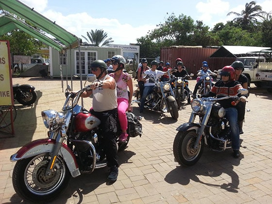 several pairs of people going on a tour of Bonaire on Harley Davidson motorcycles