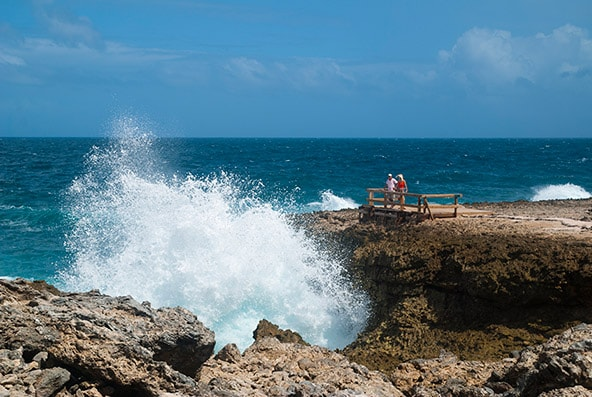 tourist watching waves crash onto rock formations at Shete Boka National Park