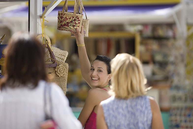 woman buying a straw bag as a souvenir