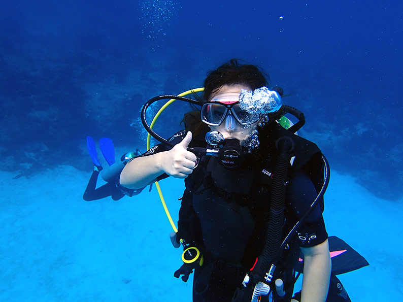 woman giving a thumbs up during a scuba dive in Bonaire