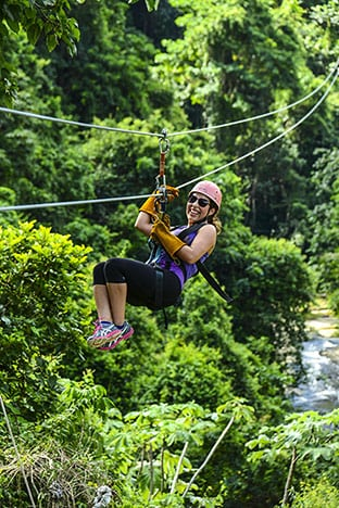woman laughing as she zip lines in la romana