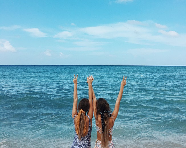 Tess & Sarah give peace sign in front of ocean
