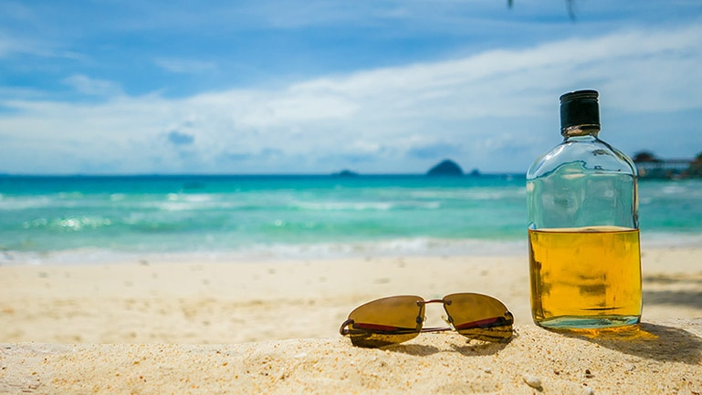 bottle of jamaican rum and sunglasses on the beach