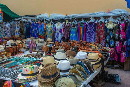 several caribbean dresses and souvenirs for sale on the street