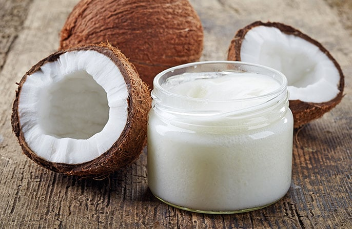 coconut oil in a glass next to a pair of coconuts