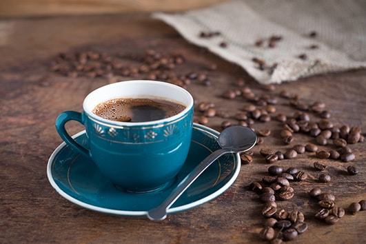 blue cup of jamaican coffee with coffee beans scattered on the table