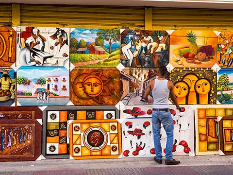 man looking at local paintings sold on the street